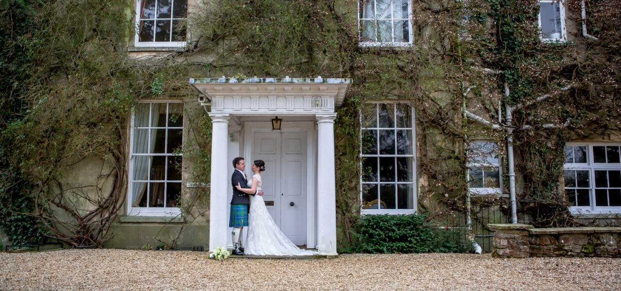 Lovely shot of the happy couple and main house at Northbrook Park